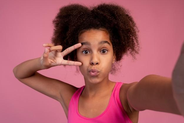 Девушка с вьющимися волосами, делающая селфи