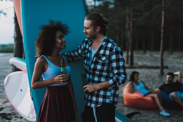 Girl with curly hair talks to guy. surf party concept.