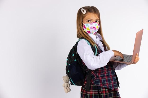 Covid-19検疫と封鎖の後に学校に戻るカスタムフェイスマスクを持つ少女。学校のフォームとラップトップを手に。