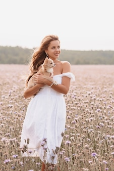 Girl with cute dog long-haired chihuahua outdoors in summer in the field
