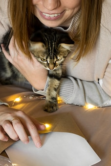 Girl with a cute kitten smiles and reads a christmas greeting in a letter.