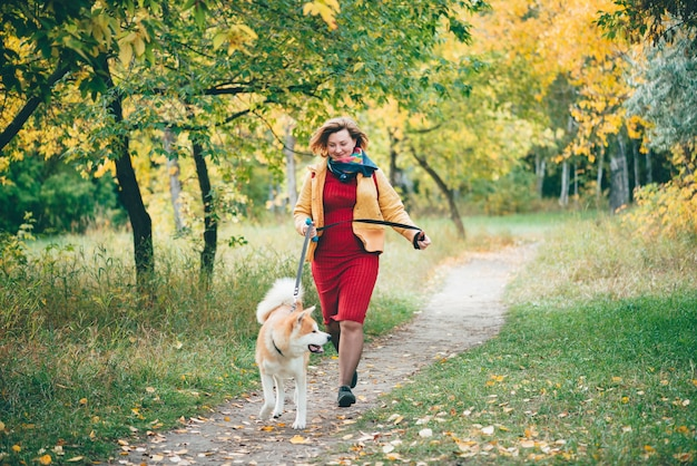 귀여운 젊은 폭시 강아지와 소녀는 가을 공원에서 단풍 사이 통로를 따라 실행