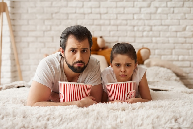 Girl with dad eat popcorn with uncomprehending.