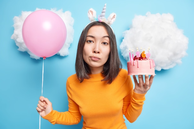 Girl with dark hair holds delicious strawberry cake and inflated balloon looks calm at camera wears casual clothes isolated on blue