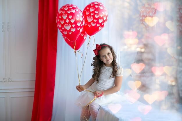 ハート型の風船のある軽いドレスを着た黒髪の少女。かわいい遊び心のある子。感情的な肖像画のコンセプトです。バレンタイン・デー。