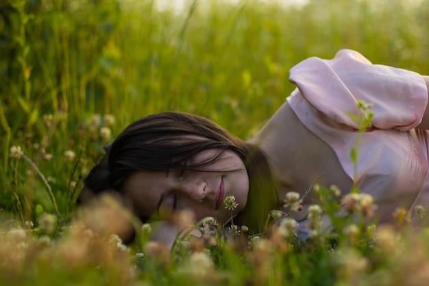 핑크색 드레스에 검은 머리를 가진 소녀는 따뜻한 여름 저녁에 흰 클로버 꽃과 함께 푸른 잔디에 누워 잔다.