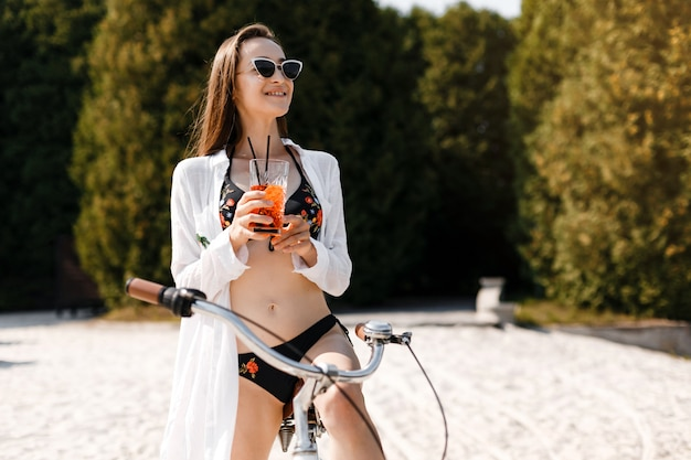 A girl with dark hair and a white blouse stands on the beach with a bike and a cocktail in her hands.