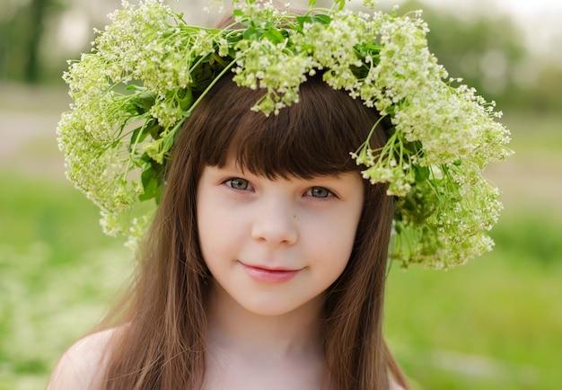 Девушка с темными длинными волосами и зелеными глазами с венком из цветов на голове