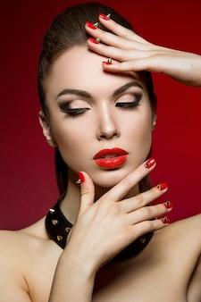 어두운 메이크업, 붉은 입술과 손톱 가시를 가진 소녀. 빨간색 배경에 스튜디오에서 찍은 사진