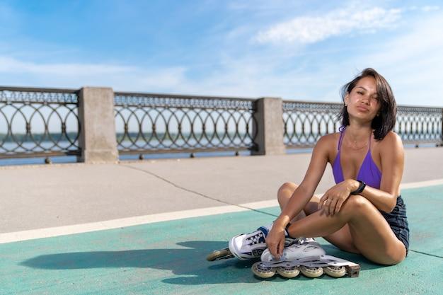 ローラースケートで肌の色が濃い女の子が歩道に足を組んで座っている