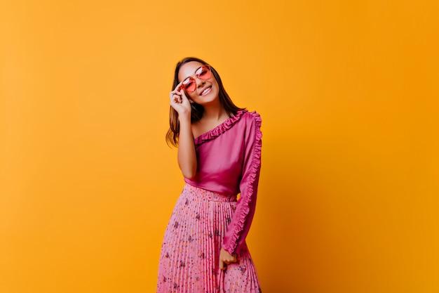La ragazza con un sorriso abbagliante in uno stato d'animo carino posa per foto in un ambiente caldo e luminoso modello in abito elegante mette gli occhiali