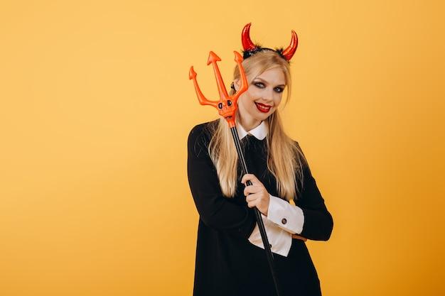 Девушка с дьявольскими рогами на голове позирует на фоне оранжевой стены