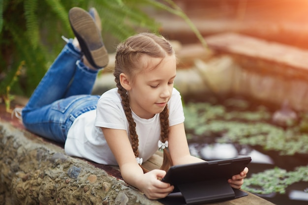 Girl with digital tablet in botanical garden