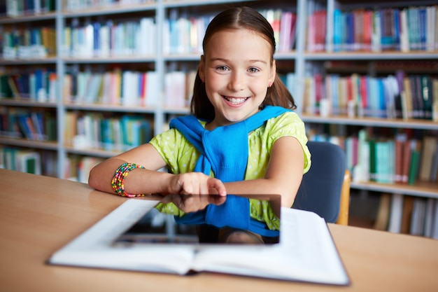 Girl with digital tablet in library