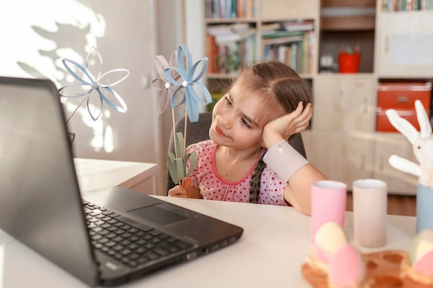 オンラインで春休み、食べる人、母の日のお祝いで家族に挨拶するdiyの花を持つ少女
