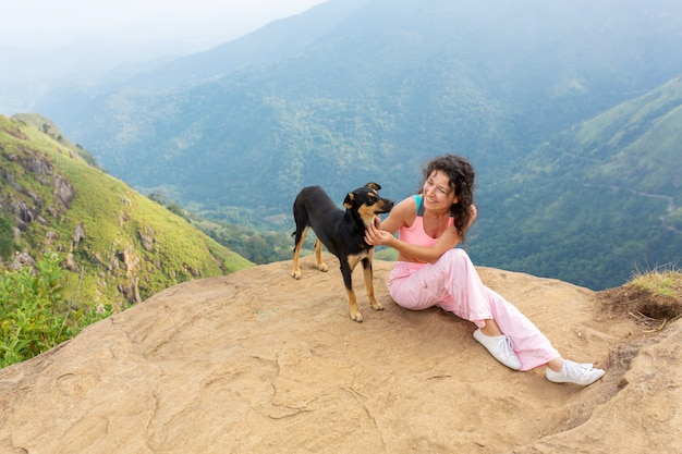 A girl with a dog enjoying the mountain scenery on the edge of a cliff