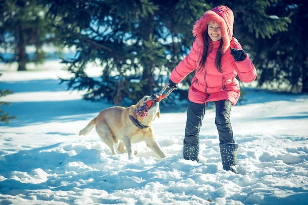 Girl with a dog labrador puppy playing in winter outdoors fun