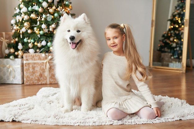 Girl with a dog near the christmas tree on the christmas background