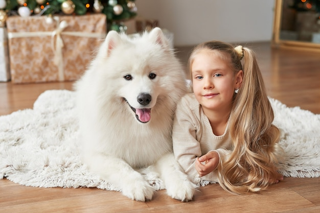 Girl with a dog near the christmas tree