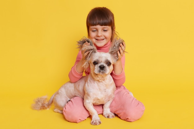 Girl with dog playing together lifts ears of puppy and laughing on yellow