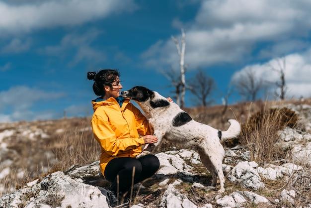 山を歩いている犬を持つ少女。犬の友達。ペットと歩いています。犬と一緒に旅行。ペット。スマート犬。親友。犬は顔をなめます。