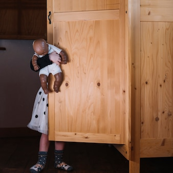 Girl with doll standing behind wooden cupboard