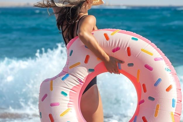 Una ragazza con un cerchio di nuoto a forma di ciambella in riva al mare. il concetto di svago e intrattenimento in vacanza.