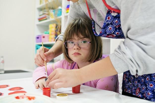 안경을 쓴 다운 증후군 소녀가 자원 봉사자의 도움으로 그립니다.