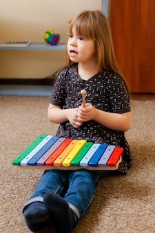Девушка с синдромом дауна играет с разноцветным ксилофоном