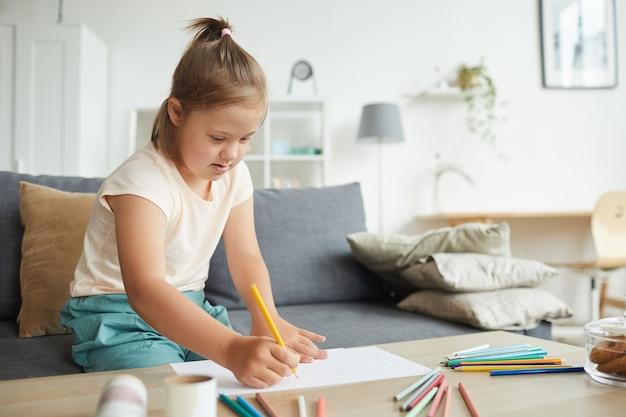 Девушка с синдромом дауна сидит за столом и рисует картину красочными карандашами в гостиной дома