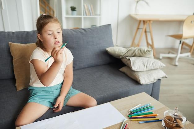 Девушка с синдромом дауна сидит на диване перед столом и учится рисовать карандашами дома