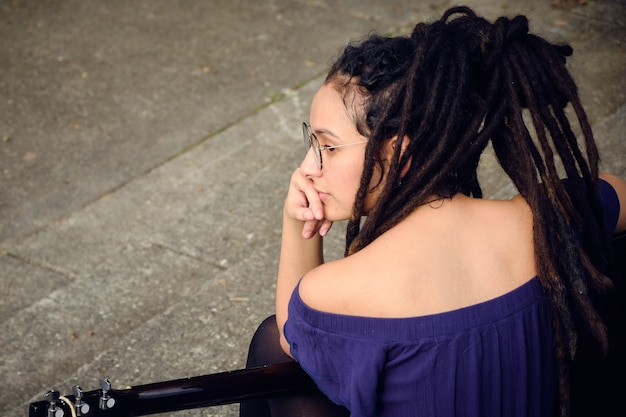 A girl with dreadlocks supported by a guitar and with her hand on her chin.