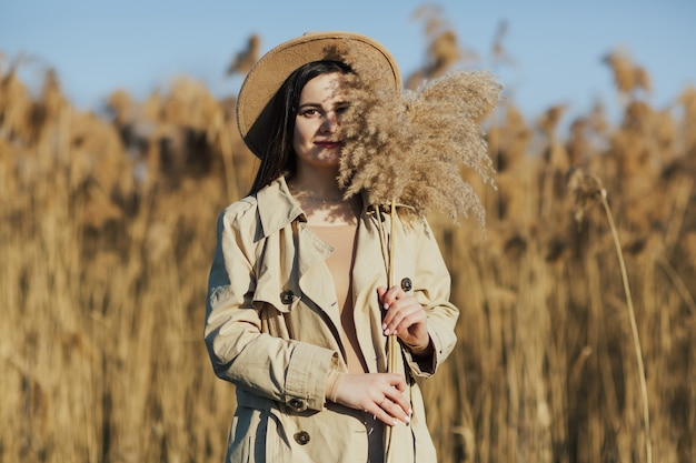 背景に乾いた葦と青い空を持つ少女