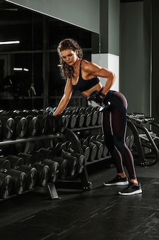A girl with dumbbells is engaged in bodybuilding on the background of the gym , a woman is engaged in fitness with dumbbells in the fitness room.
