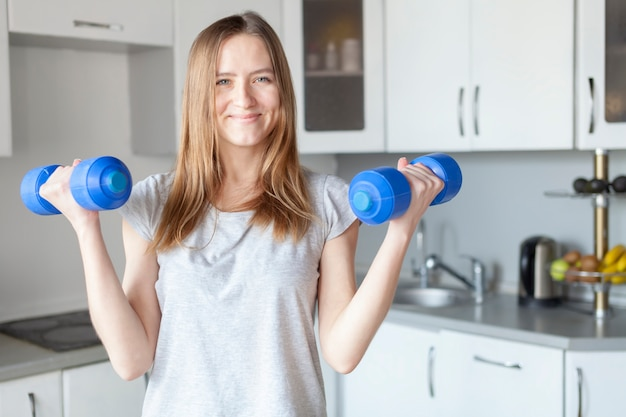 Girl with dumbbells at the kitchen smiling