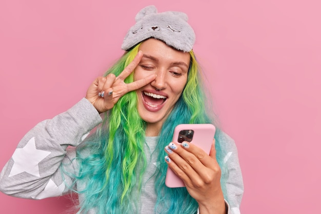 Girl with dyed hair makes peace gesture on eye holds mobile phone takes selfie wears slumber suit sleepmask on forehead poses on pink
