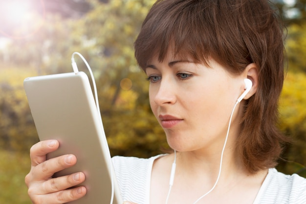 Girl with earphones looks at the tablet