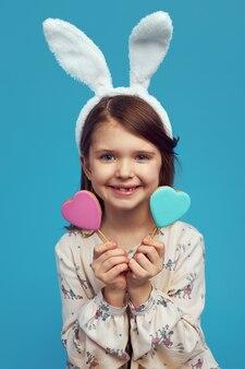 Девушка с ушками пасхального кролика с двумя печеньями в форме сердца на палочках