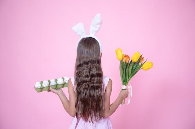 Девушка с ушками пасхального кролика держит в руках букет тюльпанов и поднос с яйцами на розовом фоне студии.