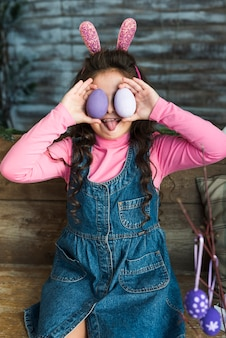 Girl with easter eggs showing tongue
