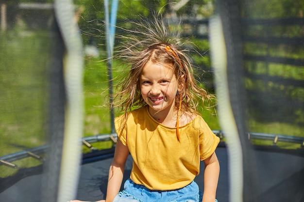 Девушка с наэлектризованными волосами на батуте на открытом воздухе, на заднем дворе дома в солнечный летний день,