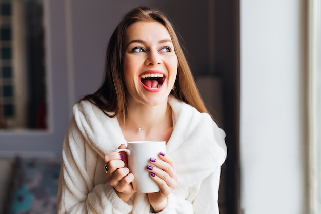 A girl with an emotional smile holding a cup of tea or coffee.