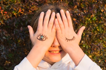 Girl with eye tattoos on hand palm covering her eyes