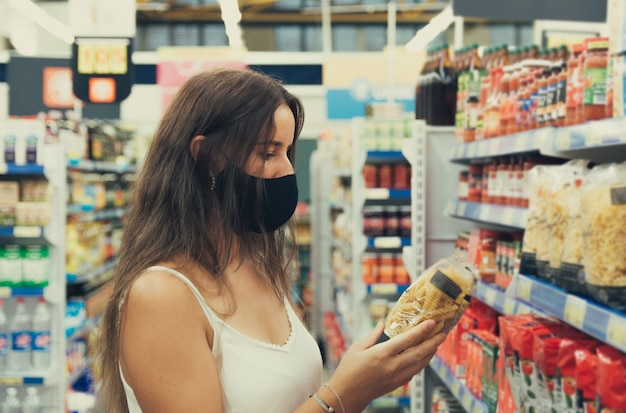Girl with a face mask looking and buying items at the supermarket.