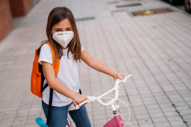 Girl with face mask riding a bike in the street during the coronavirus pandemic