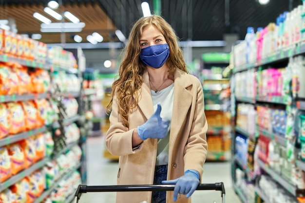 Girl with face mask show sign thumbs up and buying groceries in the supermarket during pandemic.