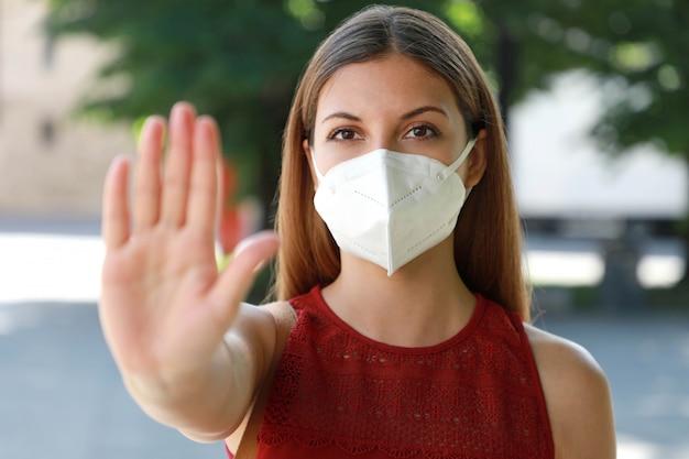 Девушка в маске показывает ладонь открытой ладони перед камерой против коронавирусной болезни 2019.