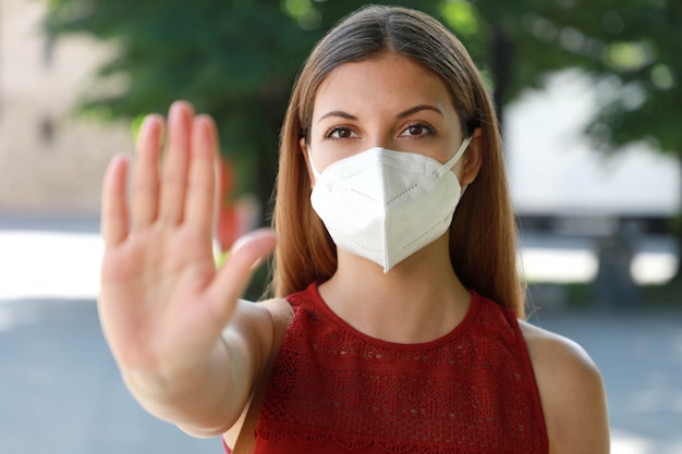Girl with face mask showing open hand palm at the camera against coronavirus disease 2019.