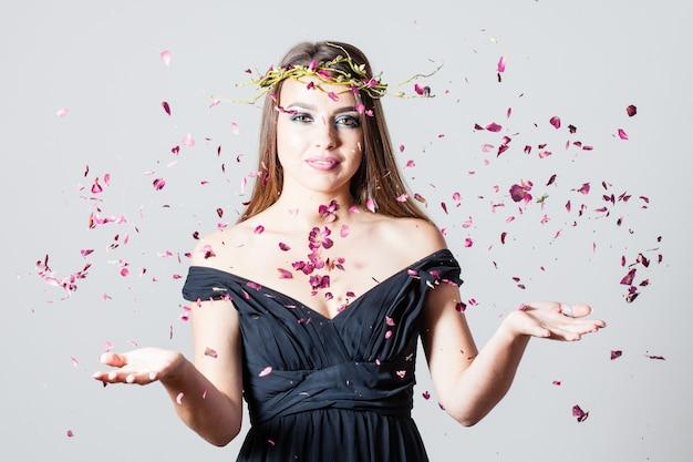 마른 장미 꽃잎이 흩어져 있는 패션 메이크업을 한 소녀