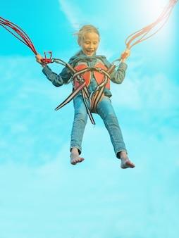 Девушка со страхом стреляет связанными ремнями на голубом небе.